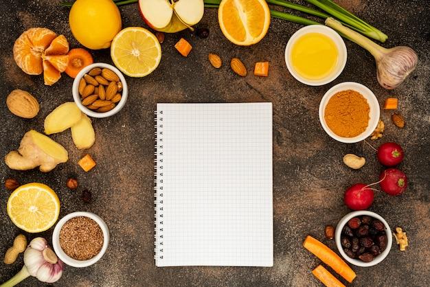 Блокнот с белым экраном вокруг здоровой пищи для повышения иммунитета. вид сверху, копия пространства.