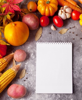 Notebook with autumn leaves and vegetables on the concrete background