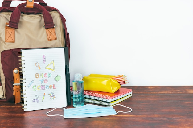 Notebook with back to school drawing. backpack and school material with mask and gel. copy space