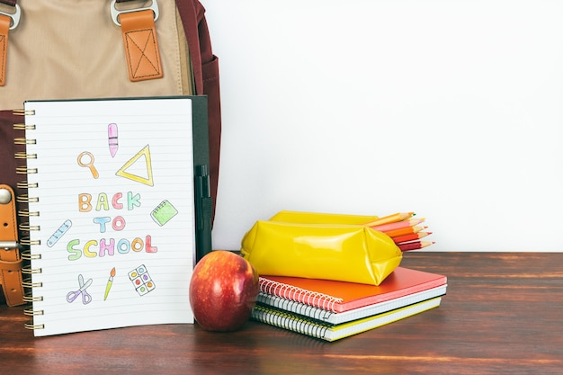 Notebook with back to school drawing. backpack and school supplies with apple on white background. copy space