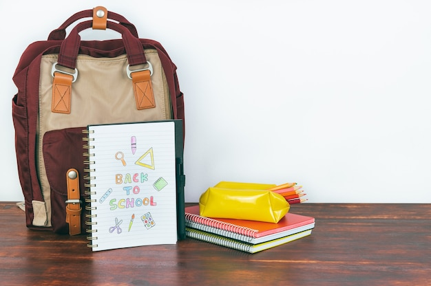 Notebook with back to school drawing. backpack and school supplies with white background. copy space