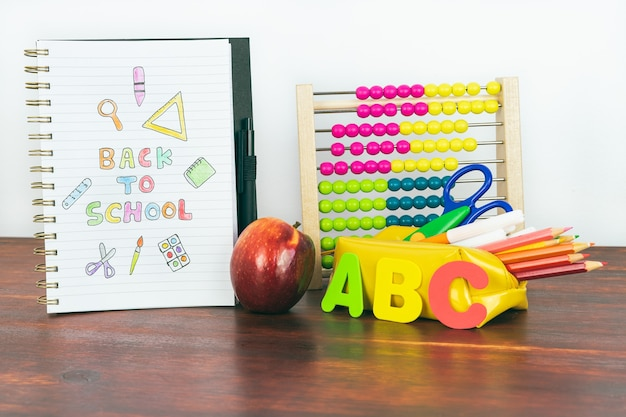 Notebook with back-to-school drawing. school material with abacus, pencils, letters and an apple. copy space