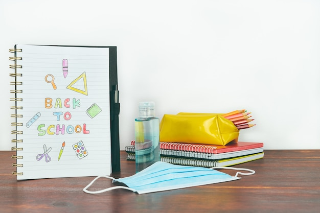 Notebook with back to school drawing. study material, mask and gel on wooden table. copy space