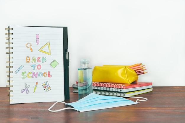 Блокнот с рисованием обратно в школу. материал исследования, маска и гель на деревянном столе. копировать пространство