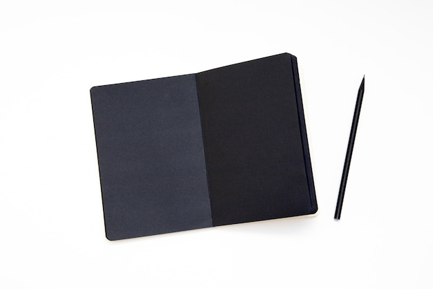 Notebook with black paper and pencil on white background.