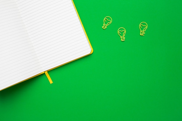 Notebook with blank pages and paperclip light bulb idea on green