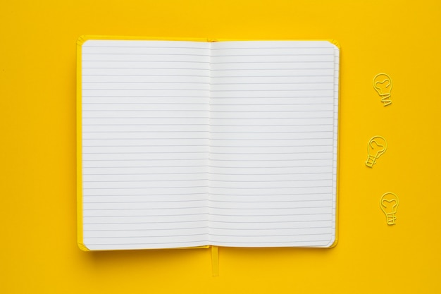 Notebook with blank pages and paperclip light bulb idea on yellow