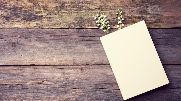Блокнот с чистыми белыми листами и букетом цветущих ландышей на деревянном столе из серых досок, вид сверху