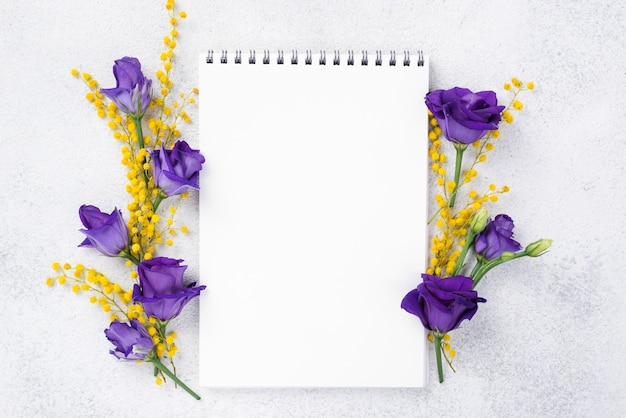 Notebook with blooming flowers beside