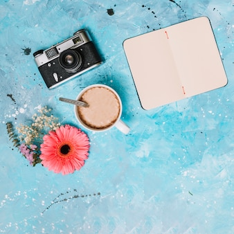 Notebook with camera, coffee and flowers on table
