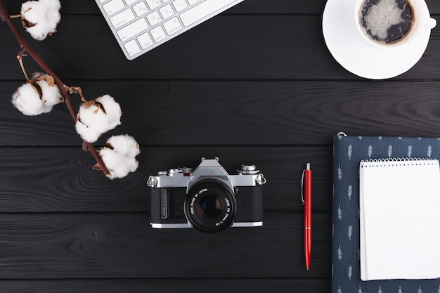 Notebook with camera and coffee on table