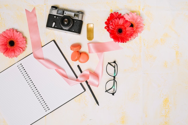 Notebook with camera, flowers and ribbon on light table