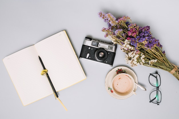 Notebook with camera and flowers on table