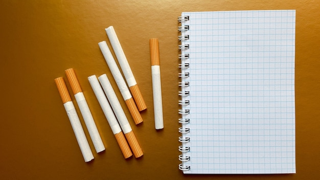 Notebook with cigarettes on top on a gold background.