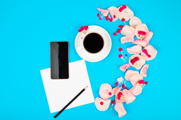Notebook with clean page, cup of coffee and pink flowers. woman working desk