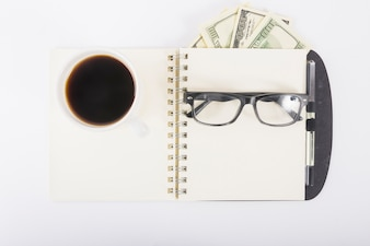 Notebook with coffee and glasses ondesk