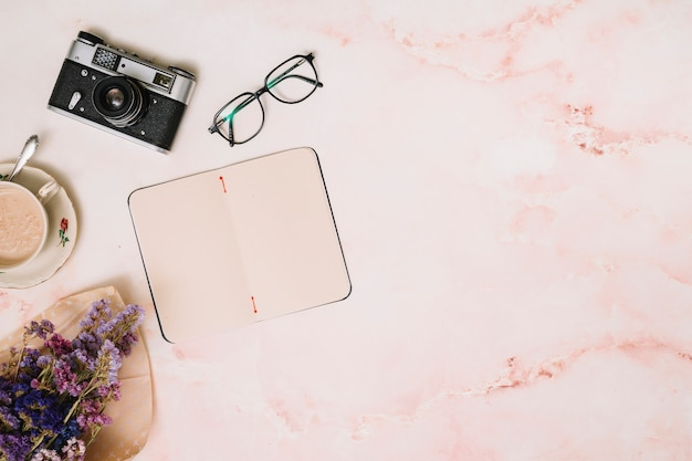 Notebook with coffee cup, camera and glasses on table