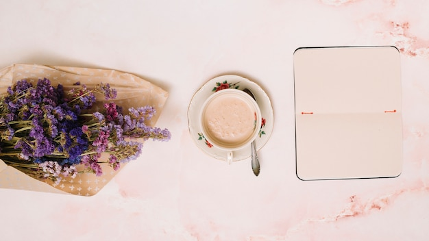 Notebook with coffee cup and flowers bouquet on table