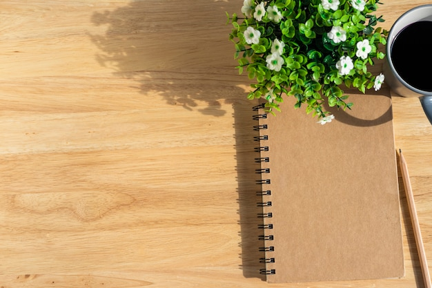 Notebook with a coffee cup and a plant on wooden table