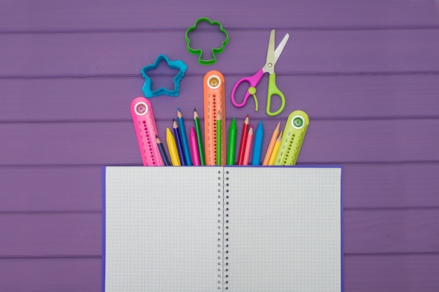 A notebook with colored pencils, rulers and scissors
