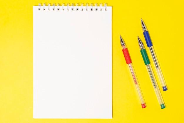 黄色の背景に色付きのペンが付いたノートブックテーブルの上のらせん状のノートブック