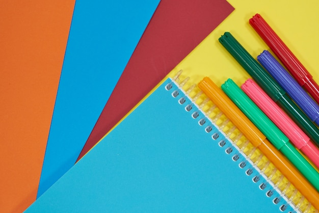 Notebook with colorful pens and papers on yellow bakcground