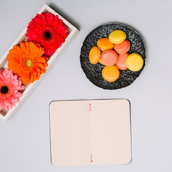Notebook with cookies and bright flowers on table