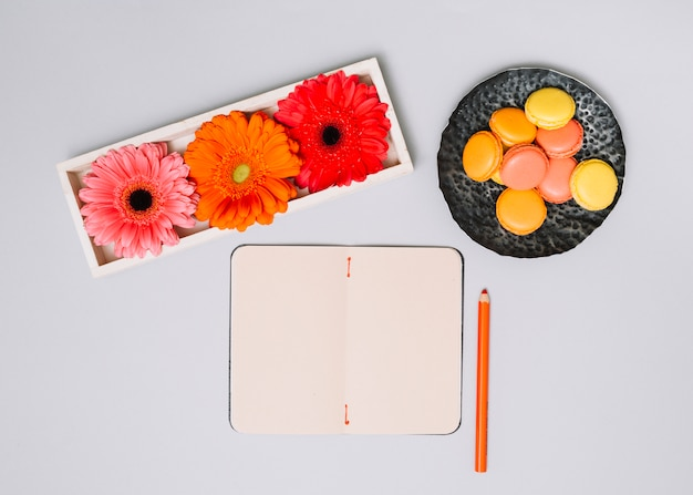 Notebook with cookies and bright flowers on white table