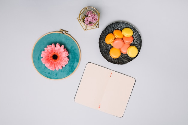 Notebook with cookies and pink flower on table