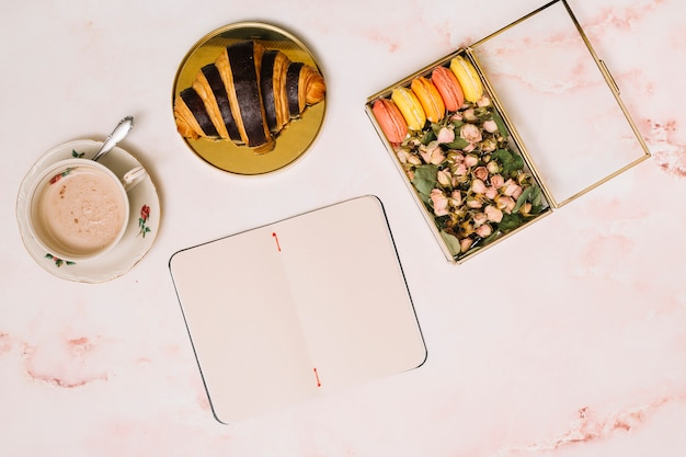 Notebook with croissant and box with flowers on table