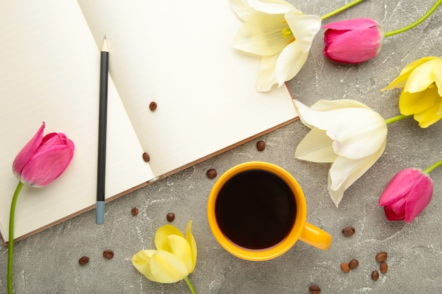 Notebook with cup of coffee and tulips on grey surface