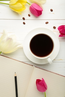 Notebook with cup of coffee and tulips on light surface