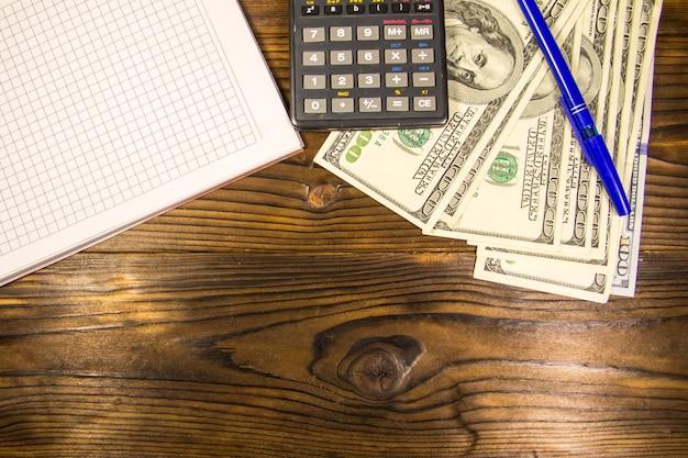 Блокнот с долларами, ручкой и калькулятором на деревянном столе. финансовая концепция