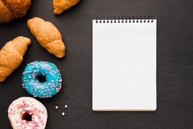 Notebook with doughnuts and croissant