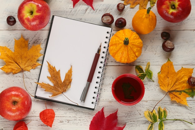 Notebook with dry leaf, apples, pumpkin, cup of tea