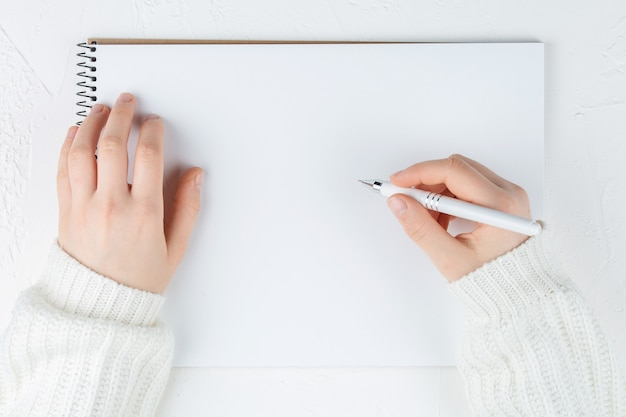 Notebook with empty sheet on a white wall with pen in hands, top view. flat lay with copy space.