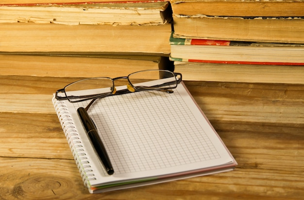 Notebook with fountain pen and glasses on wooden desk against old books