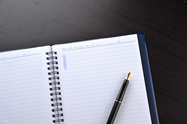 木製のテーブルに万年筆が付いているノート