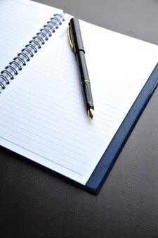 Блокнот с перьевой ручкой на деревянном столе