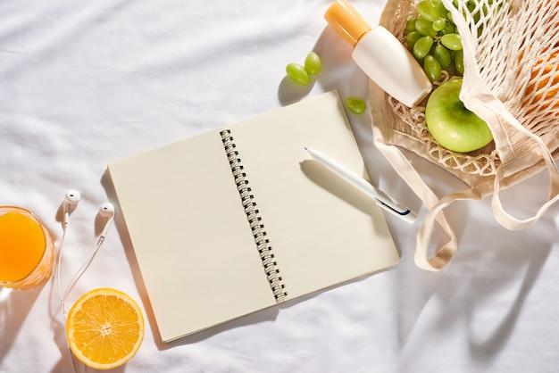 フルーツ、日焼け止めクリーム、白い布の背景にバッグとノートブック。