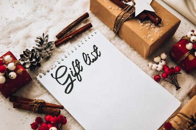 선물 목록 텍스트가 있는 노트북 하얀 눈 배경에 장식이 있는 선물이 있는 크리스마스 텍스트를 낭비하지 마십시오. 공간을 복사합니다. 공예 판지로 만든 태그가 있는 친환경 포장 선물