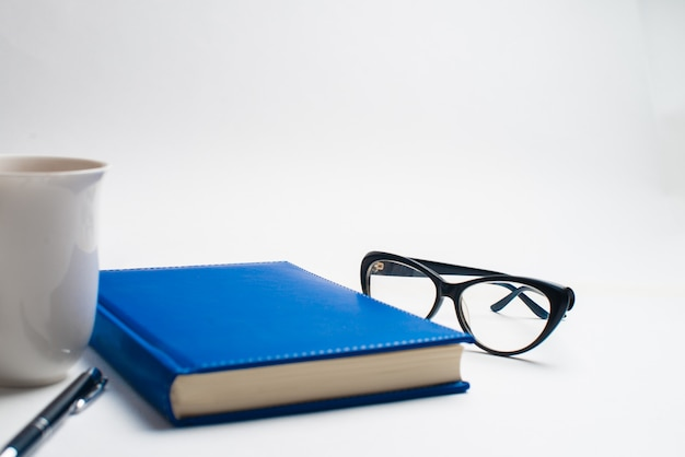 Notebook with glasses and pen, book with glasses, blue notebook with glasses, book with cup of tea