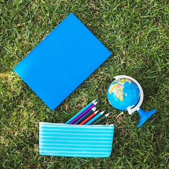 Notebook with globe and pencil case on grass
