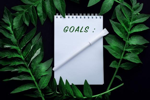 Блокнот с целями с зелеными листьями в стиле плоской планировки