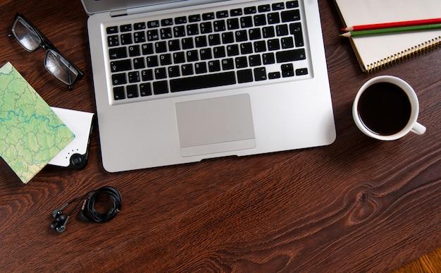 ホットコーヒーと木のテーブルの地図とノート