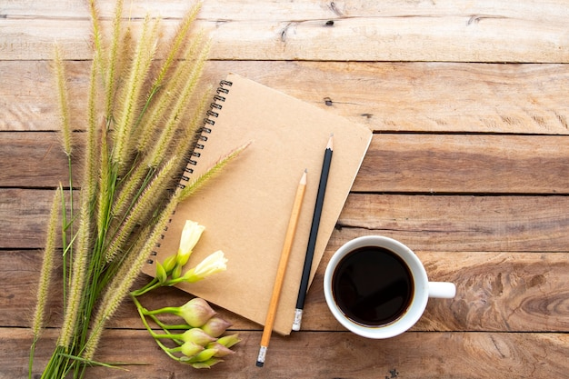 Notebook with hot coffee on background wooden