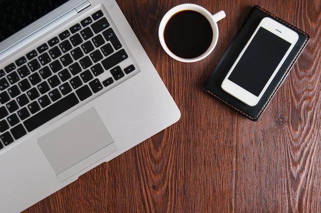 木製のテーブルでホットコーヒーとノート