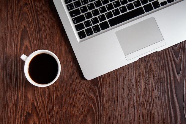 나무 테이블에 뜨거운 커피와 노트북
