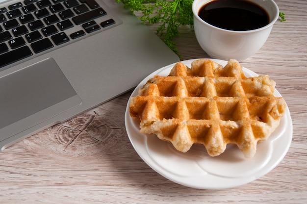 木製テーブルの上のウェーハとホットコーヒーのノート