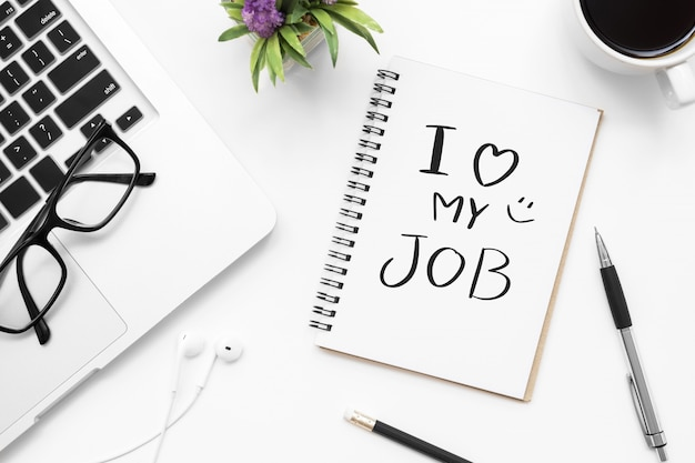 Notebook with i love my job text is on the white office desk table with supplies.